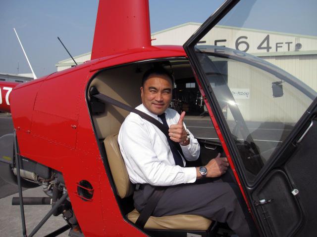 ヘリコプター免許を手にしてとてもうれしそうです